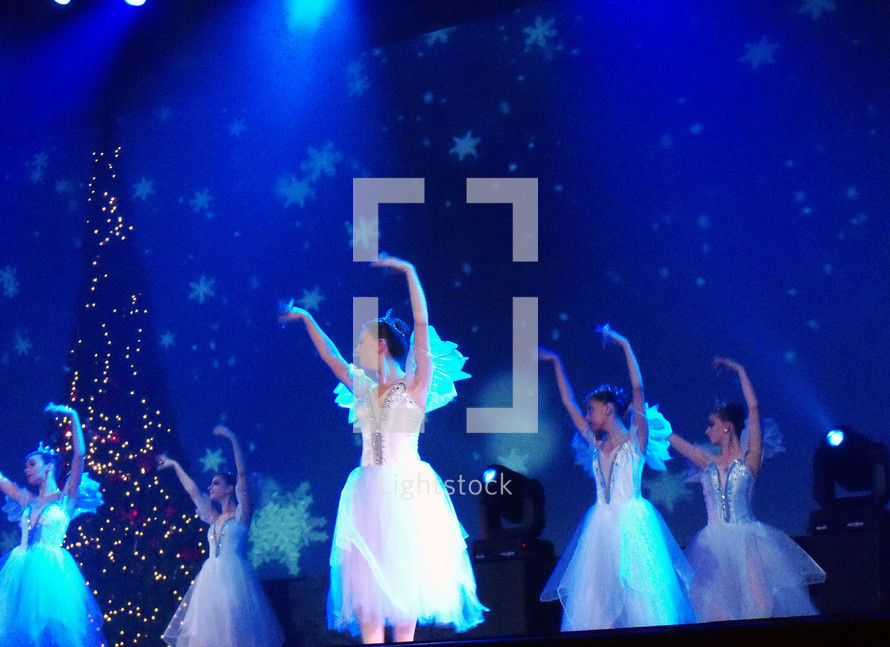 A group of female ballerina dancers from the Ukraine dance on stage wearing white outfits while surrounded by blue light and snowflake light effects on stage during a performance of The Nutcracker Christmas performance at a local church.