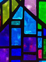 A close-up view of a stained glass window panel with vivid shades of blue, green and purple colors adorning a church sanctuary.