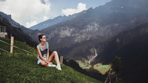 a young woman sitting on a grassy mountainside