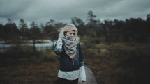 a woman covering her face with a scarf outdoors
