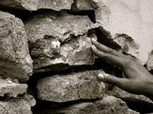 hand placing a stone in a wall