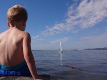 child watching a sailboat