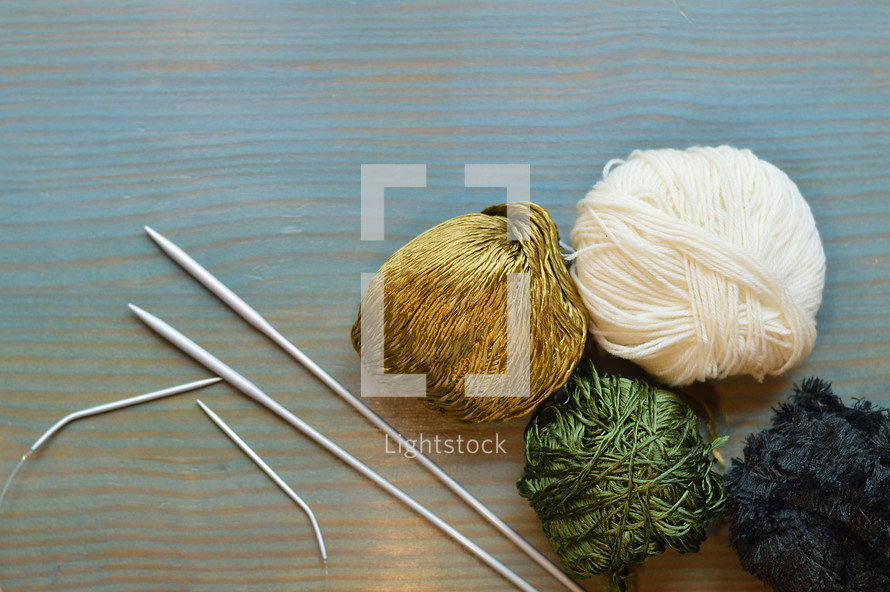 balls of yarn and knitting needles on a cyan table