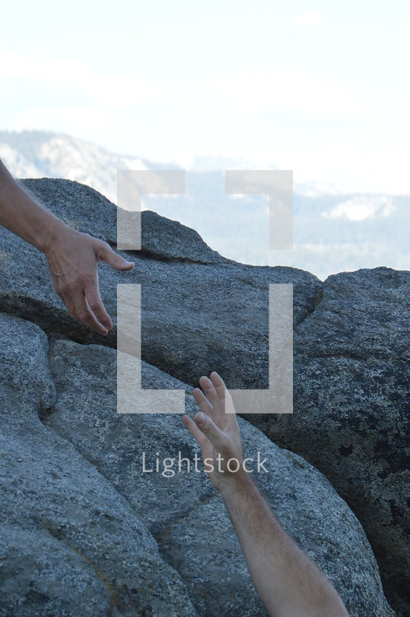 Helping hand to the top of a high rock.