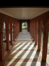 A long hall or corridor shows archways where columns of sunlight penetrate and light the path of this hallway in a church in the southeastern United States.