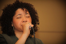 A woman with a microphone singing a worship song.