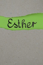 torn open kraft paper over green paper with the name of the book Esther