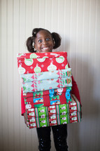 a girl child holding a stack of Christmas gifts