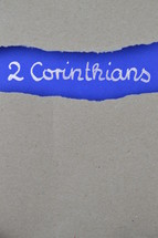 2 Corinthians - torn open kraft paper over intense blue paper with the name of the second letter from Paul to the Corinthians