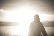Jesus standing on a shore surrounded by glowing light