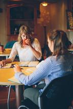 Women having a Bible study in a restaurant.