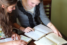 Two females studying the Bible together.