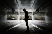 a man standing in a dark urban tunnel