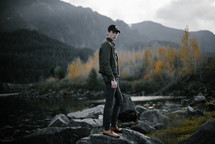 a young man in dress shoes standing on rocks by a lake