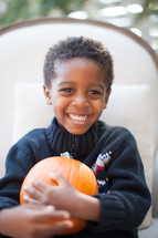 a smiling child holding a pumpkin