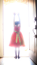 a girl child standing in sunlight from an open doorway
