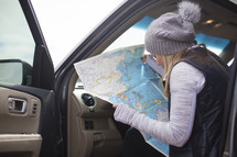 A woman studies a map while sitting in a car.