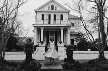 a woman in a dress twirling on a sidewalk in front of a house