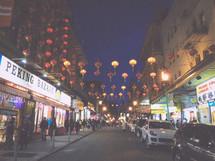 lanterns hanging over a street at night