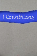 1 Corinthians - torn open kraft paper over intense blue paper with the name of the first letter from Paul to the Corinthians