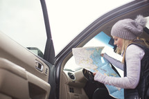 A woman looks at a map while sitting in a car.