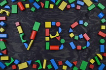 the letters VBS out of colorful wooden toy blocks on black background