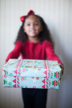 a girl child holding a wrapped Christmas gift