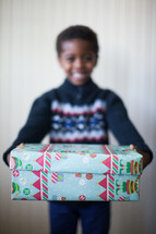 boy child holding a wrapped Christmas gift