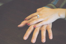 a woman's hands showing off her new engagement ring
