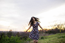 a girl walking in a meadow at sunset