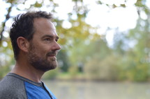 side profile of a man standing by a lake shore