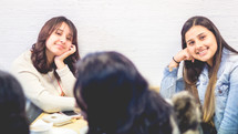 smiling young women sitting at a table