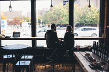 couple sitting together in a restaurant in front of a window