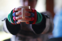 Coffee cup, held out with hands and mittens