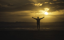silhouette of a man with arms raised standing on a beach at sunset