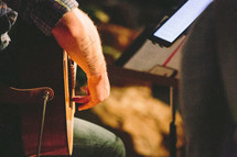 Shot of a man's arm wrapped around a guitar, music stand in front of him