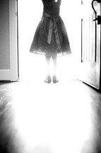 a girl child in a dress standing in light from an open doorway