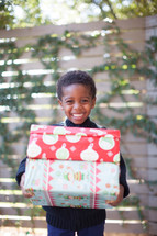 a boy child holding stacked Christmas gifts