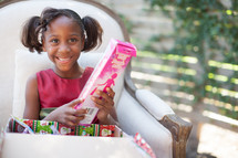 a girl child opening a Christmas gift