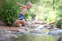 a boy child jumping into a stream in his swim suit