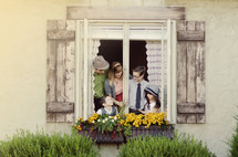 Family in a window with flower boxes.