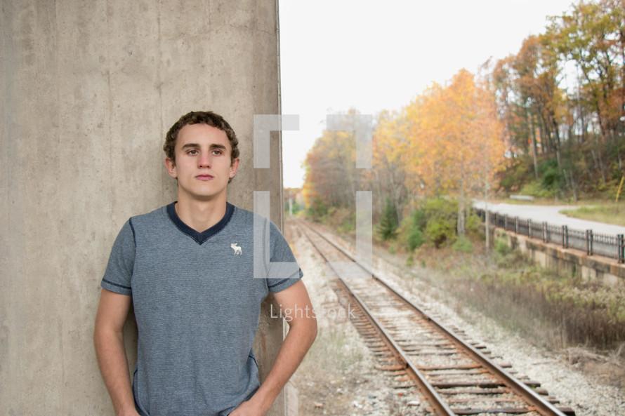 man standing near railroad tracks