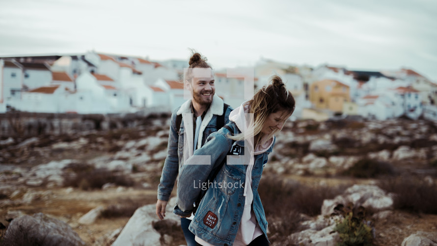 a couple walking holding hands on a beach in fall