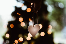 hand holding a heart ornament and bokeh Christmas lights
