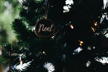noel ornament hanging on a Christmas tree