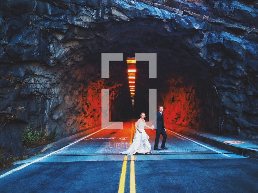 A bride and groom walking across a street in front of a tunnel.