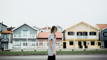 a woman walking in front of striped houses