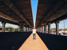A man standing under an overpass.