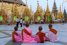 Novice monks sitting in from of a Buddhist pagoda