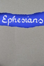 Ephesians - torn open kraft paper over intense blue paper with the name of the letter from Paul to the  Ephesians